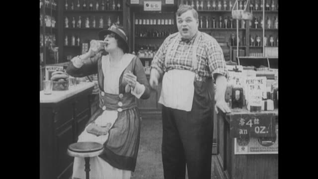 1917 a woman is so taken by the scent of a fragrance a drug store clerk (fatty arbuckle) sprays that she happily drinks it - fatty arbuckle stock videos and b-roll footage