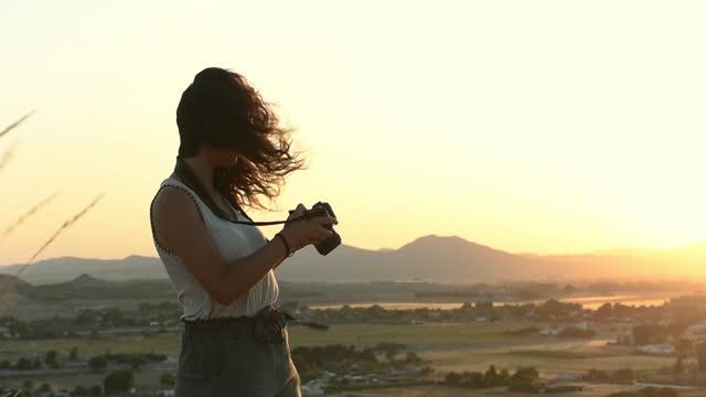 vídeos de stock, filmes e b-roll de mulher está tirando uma foto com sua câmera no topo de uma montanha - savana