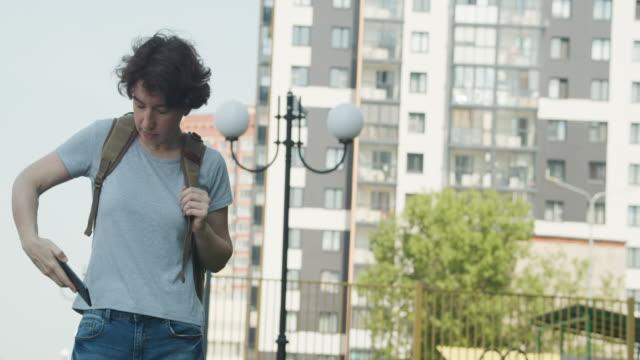 stockvideo's en b-roll-footage met de vrouw spreekt telefonisch op de straat - zak persoonlijk accessoire