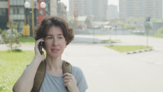 woman is talking by phone on the street - one mature woman only stock videos & royalty-free footage