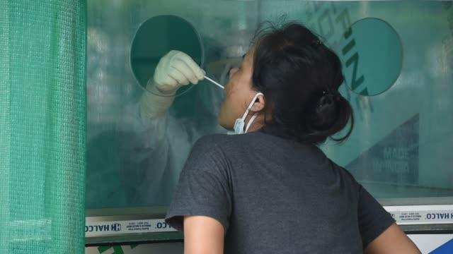 woman is tested a swab collection centre during the total lockdown imposed by the assam government to curb the spread of the novel coronavirus on... - patientin stock-videos und b-roll-filmmaterial