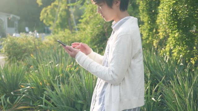 woman is using a smartphone in city - 横顔点の映像素材/bロール