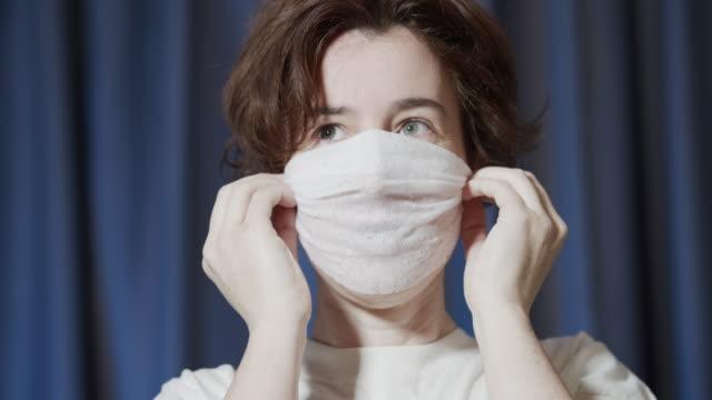 女性は彼女の顔をマスクするために濡れたワイプを使用しています - 東ヨーロッパ民族点の映像素材/bロール