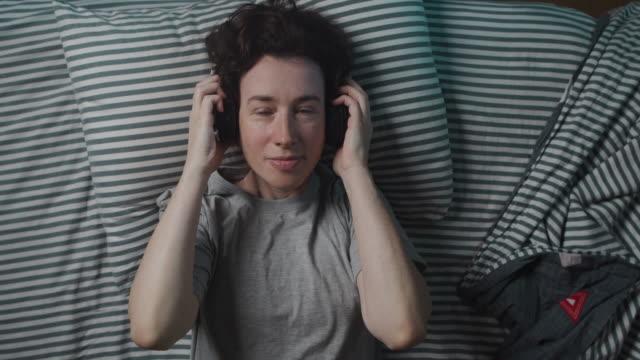 vídeos de stock, filmes e b-roll de mulher está usando fones de ouvido antes de dormir - simplicidade