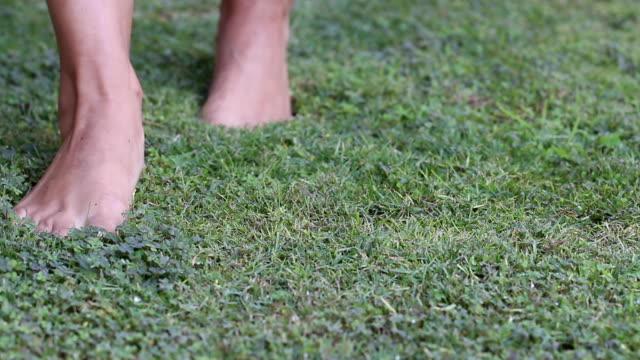 vídeos de stock, filmes e b-roll de mulher é andar descalço na grama e para na frente da câmera - descalço