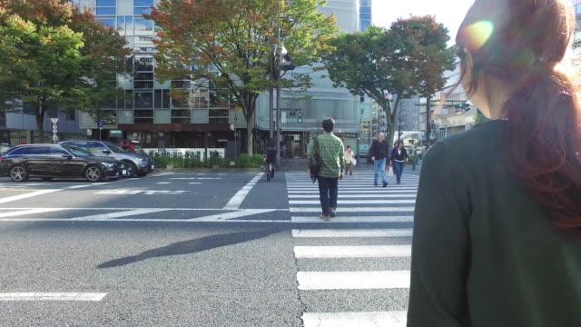 woman is walking down the street - över axel perspektiv bildbanksvideor och videomaterial från bakom kulisserna