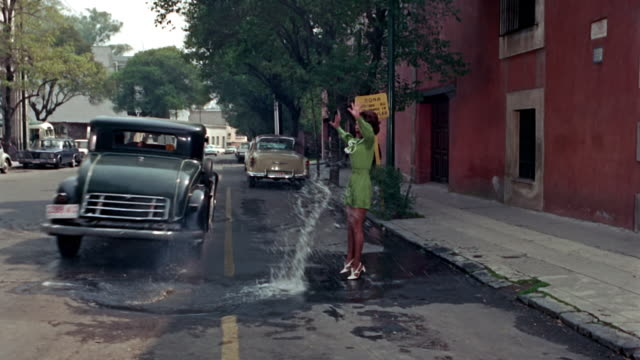 a woman is walking on a mexico street in the 1960s vintage car drives past her through a puddle splashing her with dirty water - actor stock videos & royalty-free footage