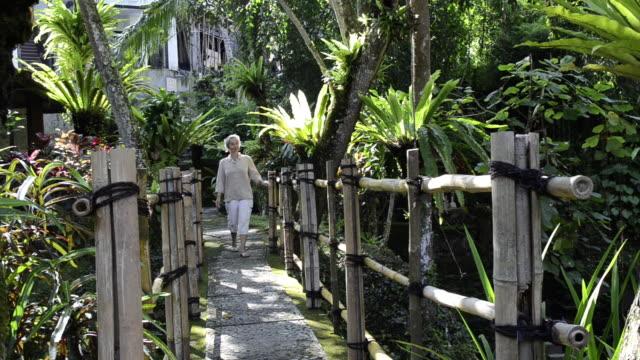 ms woman is walking over bridge in tropical garden / ubud, bali, indonesia - ubud district stock videos & royalty-free footage