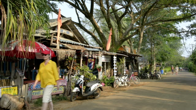 a woman is walking through a picturesque thai village with restaurant - 村点の映像素材/bロール