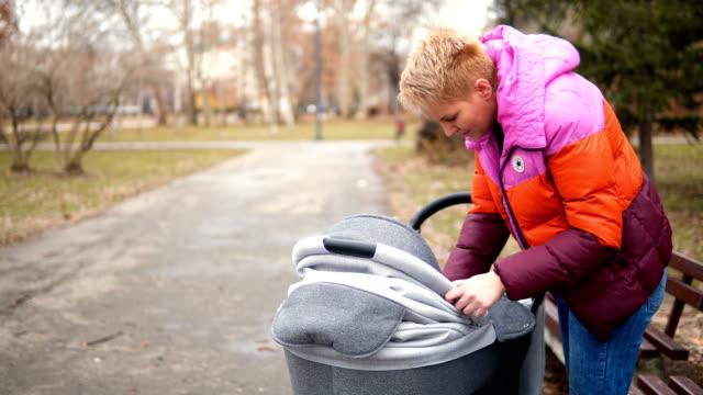 女性が公園でベビーカーで赤ちゃんと一緒に歩いています。 - 30代点の映像素材/bロール
