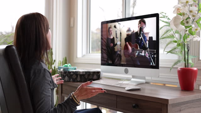 a woman is watching an online music concert from home for her birthday during covid-19 pandemic - stream stock videos & royalty-free footage