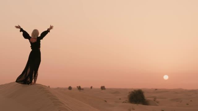 vídeos y material grabado en eventos de stock de la mujer está viendo la puesta de sol en el desierto - vestido