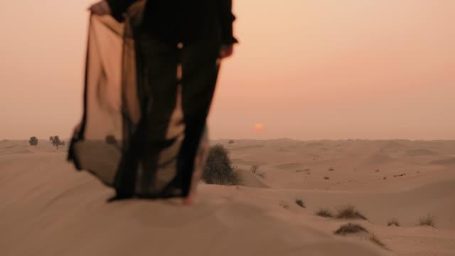 女性は砂漠で夕日を見ている - differential focus点の映像素材/bロール
