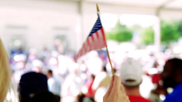 woman is waving american flag during fourth of july parade - american flag stock videos and b-roll footage