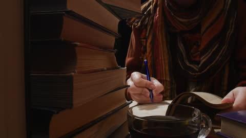 kvinna arbetar med pappersböcker vid skrivbordet - varmt ljus bildbanksvideor och videomaterial från bakom kulisserna