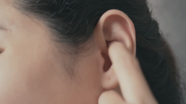 kvinnan kliande och repor på hennes öra. hälsovård och medicinska koncept. - öra bildbanksvideor och videomaterial från bakom kulisserna