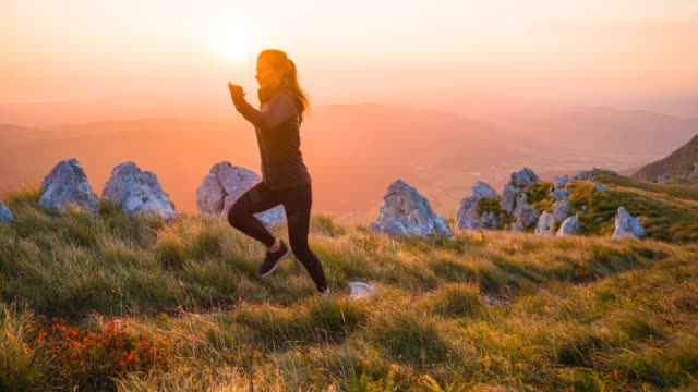 Woman jogger running in mountains at sunset