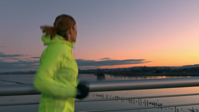 SLO MO Woman jogging across the bridge at sunset