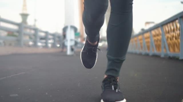 橋を渡ってジョギング mo 女性、低角度ビュー - 決意点の映像素材/bロール
