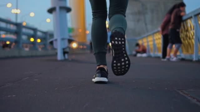 低角度のビュー ・ ブリッジを渡るジョギング slo mo 女性 - 決意点の映像素材/bロール