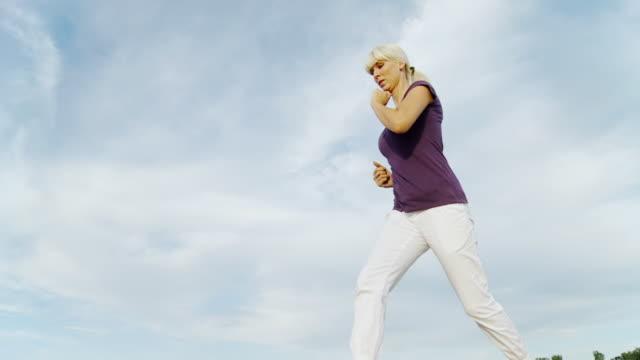 HD SLOW MOTION: Woman Jogging Against Sky