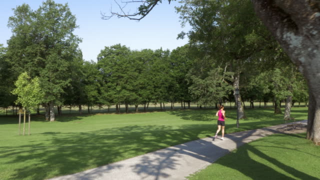 vídeos y material grabado en eventos de stock de antena mujer trotar junto al lago en el parque - sin mangas