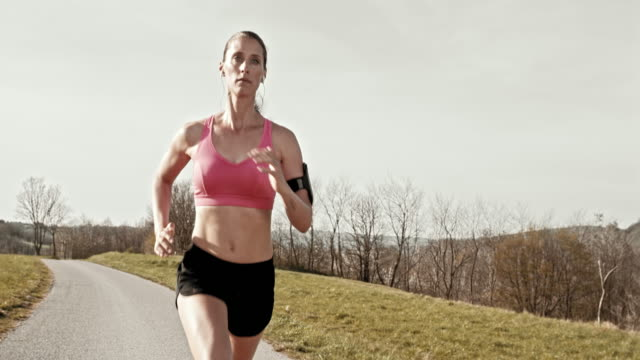 SLO MO TS Woman jogging along a road
