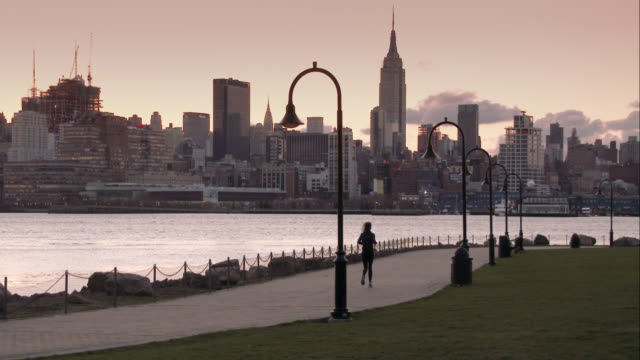 Woman Jogging Along Hudson River on a Path in Hoboken Overlooking the Midtown Manhattan Skyline