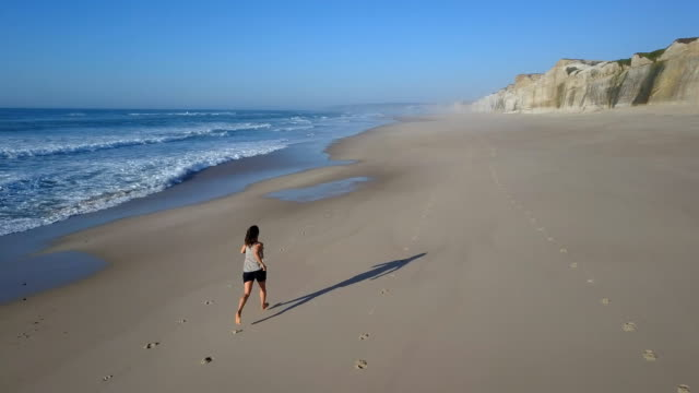 woman jogging along the beach back view - coastal feature stock videos & royalty-free footage