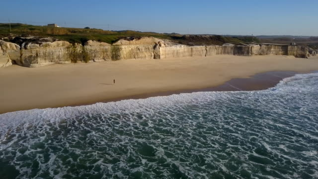 vídeos de stock e filmes b-roll de woman jogging along the beach filmed sideways - atividade desportiva