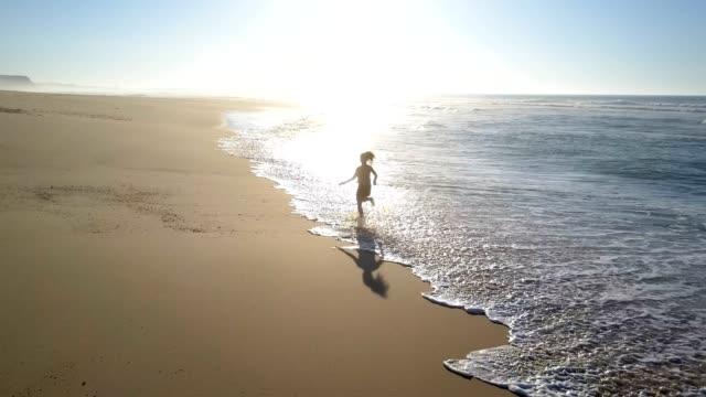 vídeos y material grabado en eventos de stock de mujer para correr a lo largo de la salpicadura de agua de la playa - aerobismo