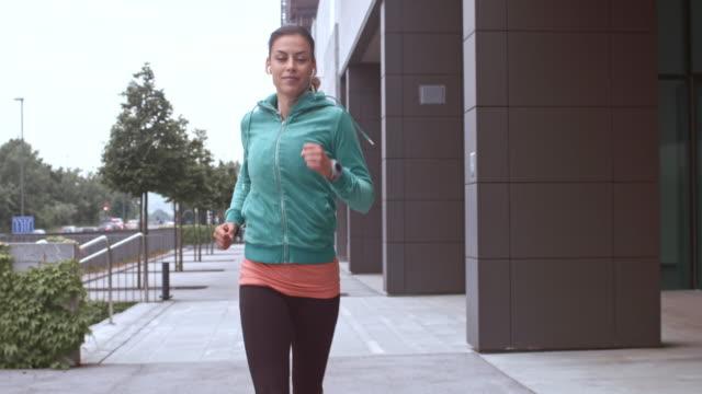 slo mo-ts frau joggen in einem business-gebäude - vorderansicht stock-videos und b-roll-filmmaterial