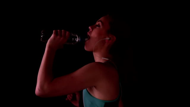 Woman jogging and drinking water while listening to music