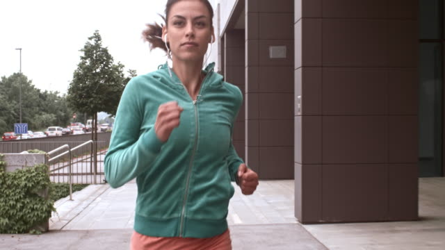 SLO MO TS Woman jogging and listening to music