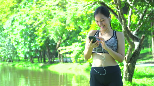 kvinna joggar och använder den smarta telefonen - 10 seconds or greater bildbanksvideor och videomaterial från bakom kulisserna