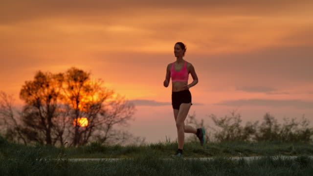 slo mo ts woman jogging at sunset - running shorts stock videos and b-roll footage
