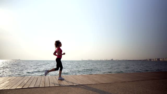 woman jogging by the sea - side view stock videos & royalty-free footage