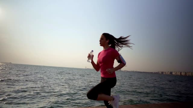woman jogging by the sea - outdoor pursuit stock videos & royalty-free footage