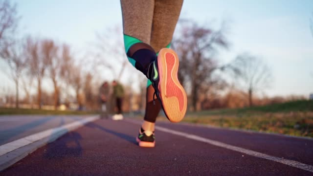 woman jogging during sunset - sports track stock videos & royalty-free footage