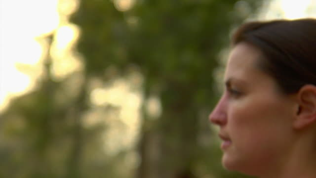 slo mo cu ts woman jogging in forest, wilmington, north carolina, usa - 横顔点の映像素材/bロール