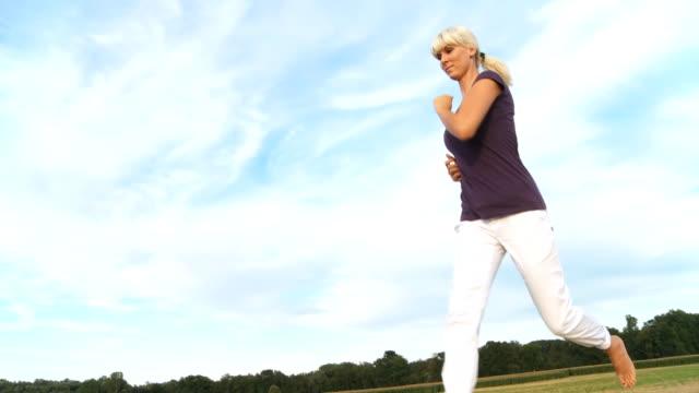 vídeos de stock, filmes e b-roll de hd estáveis foto: uma mulher correndo na natureza - perfil vista lateral