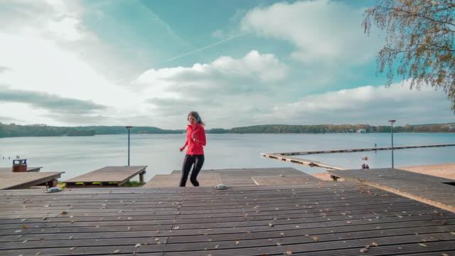 stockvideo's en b-roll-footage met vrouw joggen in het park - huppelen