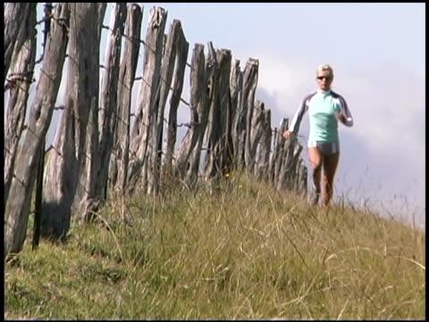 woman jogging in rural field - einzelne frau über 30 stock-videos und b-roll-filmmaterial