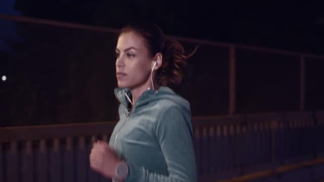 slo mo-ts frau joggen in der stadt bei nacht - drehort außerhalb der usa stock-videos und b-roll-filmmaterial