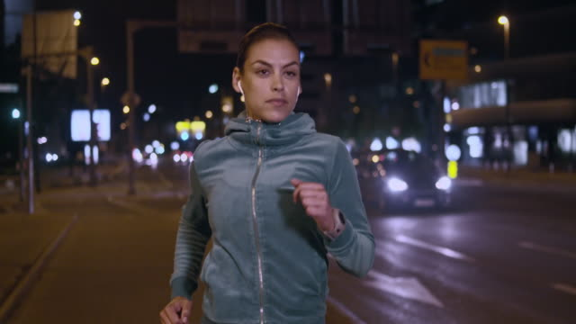 SLO MO TS Woman jogging in the city street at night