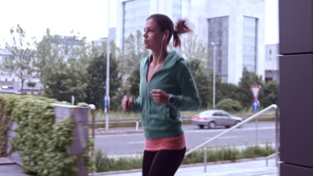 slo mo ts woman jogging in the city - jogging stock videos & royalty-free footage