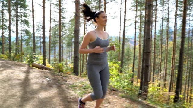 Femme jogging dans la forêt.