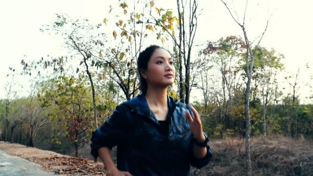 woman jogging in the park, concept exercise, slow motion - solo una donna di età media video stock e b–roll