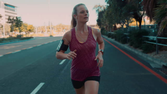 woman jogging in urban setting - smart watch stock videos & royalty-free footage