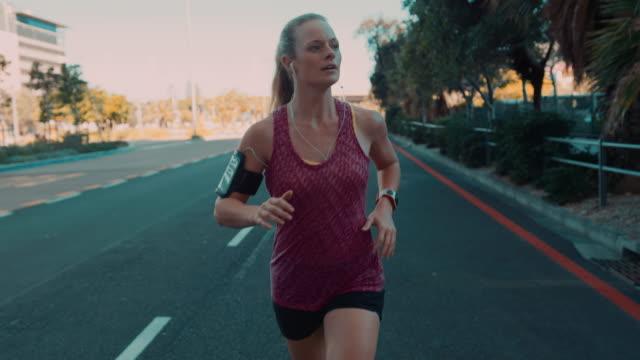 frau joggen in urbaner atmosphäre - kopfhörer stock-videos und b-roll-filmmaterial
